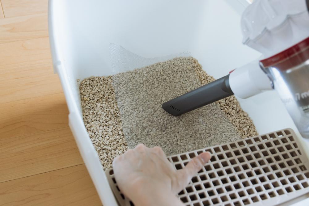 網越しに猫砂に掃除機をかける様子